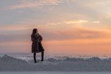 Girl with long straight hair in a fur coat against the background of a winter evening sky - 183907198