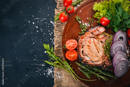 Papiers peints Steakhouse Grilled Steak, with Vegetables. Pork, veal, meat. On a wooden background. Top view. Free space for text.