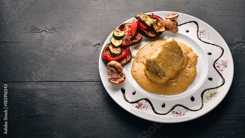 Plexiglas Steakhouse Meat steak with sauce and grilled vegetables. Steak Voronov. On a wooden background. Free space for your text. Top view.