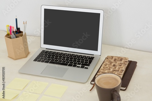 Wall mural Laptop and various office accessories on table