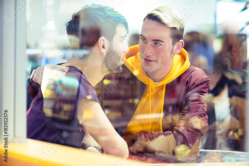 Gay couple talking together in a cafe