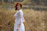 lady with red hair in vintage white dress in forest