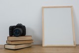 Picture frame, books and digital camera on table - 183923332