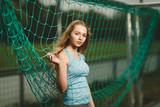 Fußballerin posiert im Netz von einem Tor - 183923961