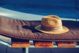 Straw hat on deck chair by the swimming pool - 183925528
