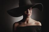 Dark studio portrait of elegant sexy woman in black wide hat and black dress. - 183926556