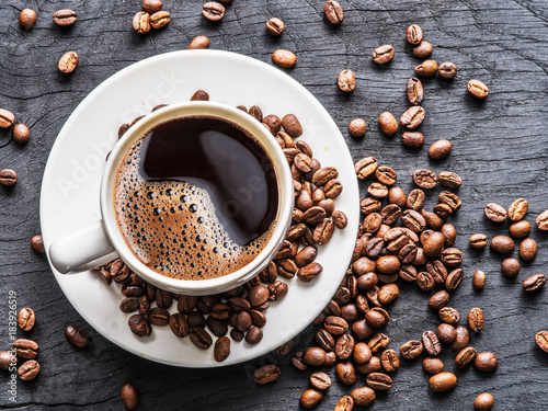 Cup of coffee surrounded by coffee beans. Top view. - 183926519