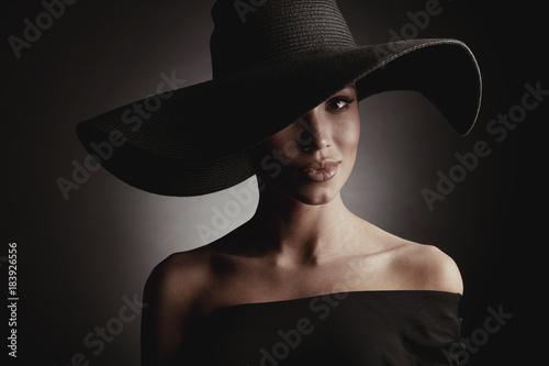 Ciemny pracowniany portret elegancka seksowna kobieta w czarnym szerokim kapeluszu i czerni sukni.
