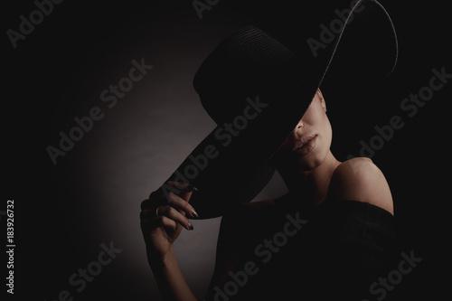 Dramatic dark studio portrait of elegant woman in black wide hat and black dress. Hidden eyes.