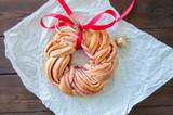 Raspberry jam swirl brioche wreath on a wooden background. - 183930159