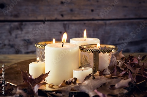 Lit candles and dry leaves on table