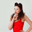 Charming lady in red corset, pin-up hairstyle. Finger at lips, Shh