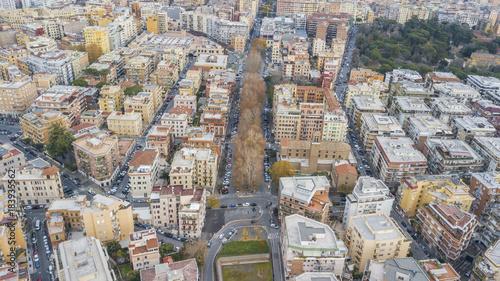 Vista aerea di una parte della citta di Roma. Tanti palazzi sono presenti tra le vie della città con qualche albero piantato nelle piazze e nei viali.