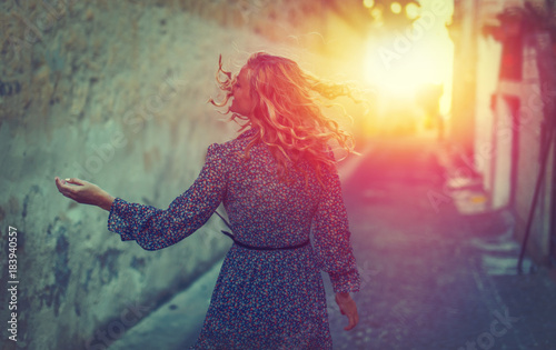 Young carefree woman walking on mediterranean street in sunset