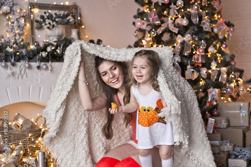 Mother and daughter hid under a blanket near the Christmas tree 9449 Poster
