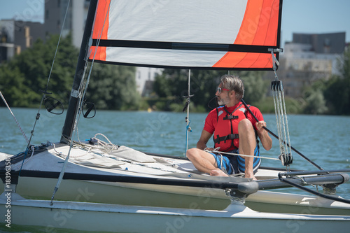 mature handsome man sailing on a lake Poster