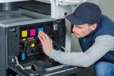 Man checking ink cartridges in photocopier - 183964343