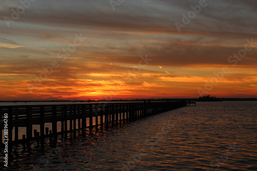Tuinposter Zee zonsondergang Sunset and a fishing pier jetty over water with reflection and cloudscape