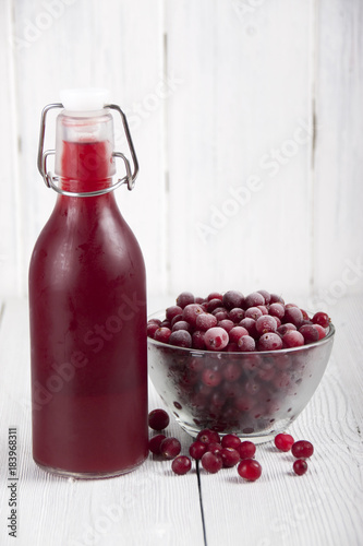 Foto op Canvas Sap Cranberry juice in a bottle and a cranberries in a glass bowl
