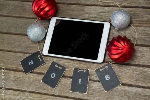 Baubles and cards forming 2018 around the digital tablet