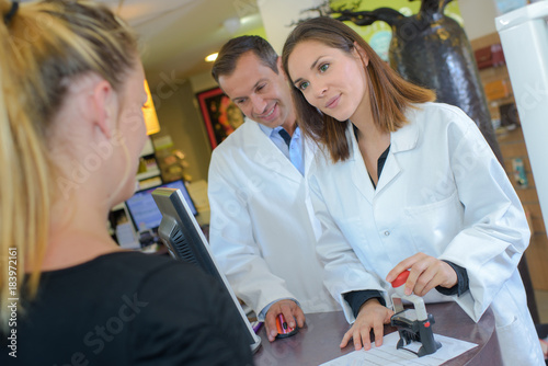 Foto op Aluminium Apotheek Pharmacist stamping customer's prescription