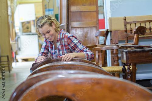 female carpenter polishing wood - 183973378