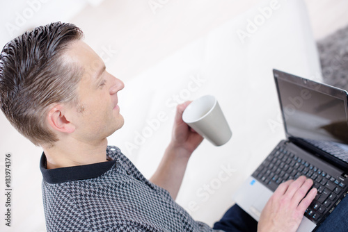 young man holding coffee cup with laptop at desk