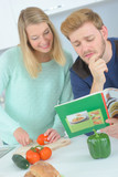 Couple looking at recipe book while chopping vegetables - 183974541