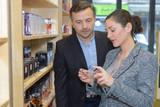 beautiful saleswoman showing beauty products to male customer - 183974559