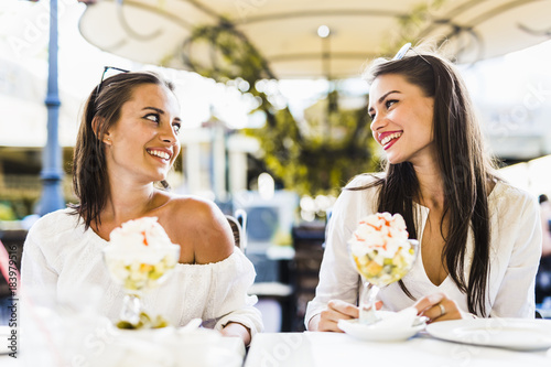 Two beautiful young women smiling and having a fruit salad in a
