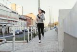 Beautiful female jogging in city - 183980150
