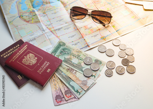 Keuken foto achterwand Abu Dhabi Arab dirhams and a Russian passport on the background of the card and sunglasses. The concept of travel.