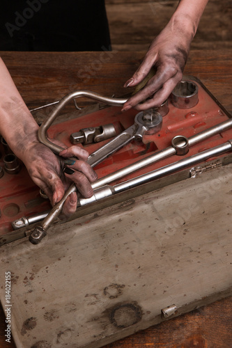 Female mechanic. Dirty woman hands looking for a needed tool in a box. Woman power - I will repair the car myself