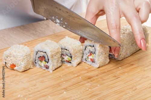 Tuinposter Sushi bar Chef cuts rolls, hands close-up