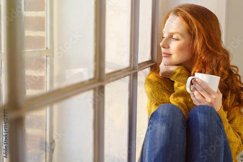 Kobieta cieszy się promieniami słońca w oknie