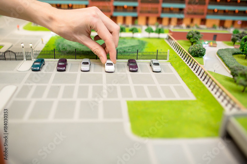 Human hand taking one of car models from parking place on layout of modern city