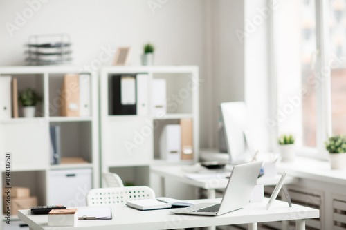 Wall mural Desk with laptop, notebook, calculator, clip box, picture frame and clipboard with paper in empty office