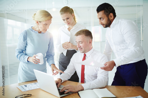 Group of confident co-workers having discussion of new project and searching for online data