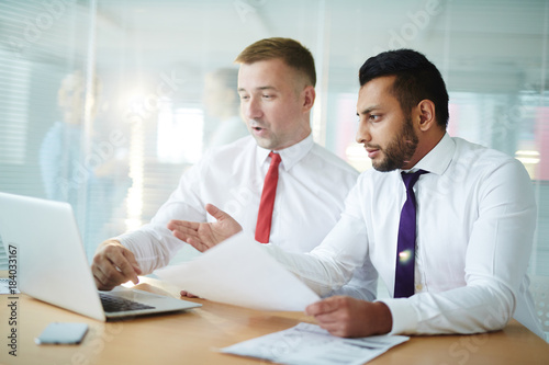 Two businessmen sitting in front of laptop and looking through online financial statistics in office