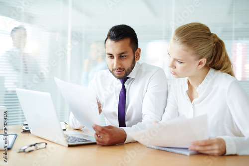 Young businessman showing paper to his colleague while working in office