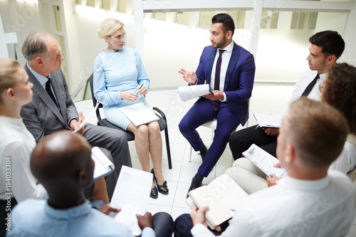 Large group of young and mature colleagues in formalwear sitting in circle at session or seminar and discussing reports