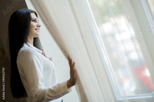 Happy beautiful woman staring out the window