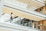 Elegant businesswoman walking inside building - 184033902
