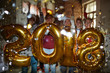 Excited guys and girls holding golden inflatable numbers and making 2018