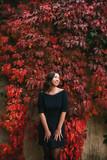 A beautiful girl is standing and smiling next to a wall decorated with autumn leaves. - 184039313