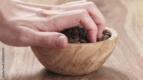 Wall mural Slow motion young man hand taking some coffee beans from bowl to check quality