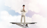 Businessman on metal tray playing fife against blue sky background - 184040754