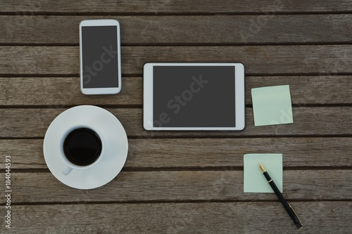 Electronic gadgets, black coffee, pen and sticky note on wooden