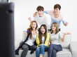 young group Sitting On Sofa Watching TV  show.