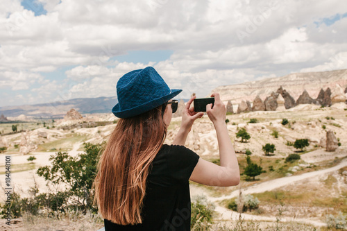 A tourist makes a photo on the phone in memory of a beautiful view of the hills in Cappadocia in Turkey. Travel, tourism, vacation.